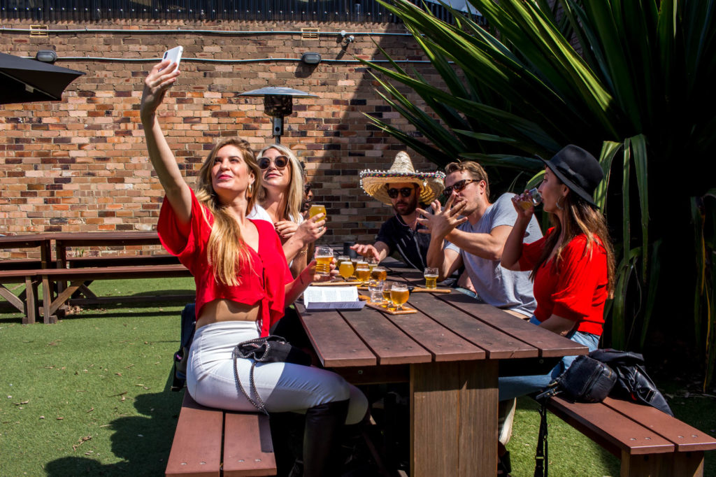 People taking selfie at microbrewery in Sydney in the beergarden of Sauce Brewing Co